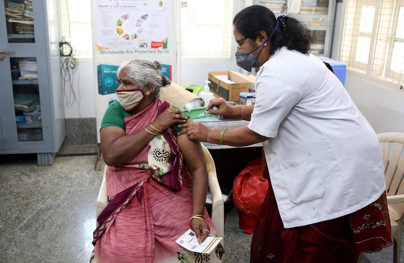 epa09076015 A woman receives a dose of a vaccine against COVID-19 during a vaccination campaign at Dasappa Hospital in Bangalore, India, 15 March 2021. India recorded its highest single-day spike this year with over 25,000 covid-19 cases reported from all over the India and mainly from Maharastra state.  EPA/JAGADEESH NV