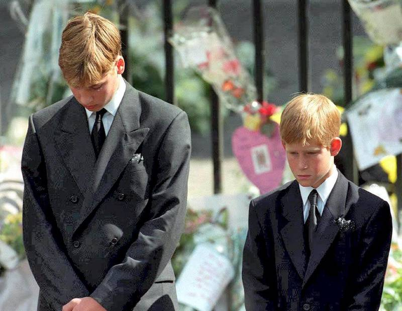 Prince William (left) and Prince Harry, the sons of Diana, Princess of Wales, bow their heads as their mother's coffin is taken out of Westminster Abbey 06 September following her funeral service. The princess was killed 31 August in a car crash in Paris. (Photo by ADAM BUTLER / POOL / AFP)