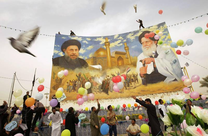 """Balloons fly as Iraqi Shiite Muslims free pigeons while holding signs reading in Arabic """"We are coming"""" during the inauguration ceremony of a renovated mural bearing the portraits of Shiite clerics Mohammed Baqer al-Sadr (L) and Mohammed Sadeq al-Sadr (R) following Friday prayers in Baghdad's Shiite bastion of Sadr City on March 5, 2010. Politicians launched into their last day of campaigning as more than a million Iraqis living abroad began voting in an election that could turn the page on years of deadly sectarian strife. AFP PHOTO/JOSEPH EID / AFP PHOTO / JOSEPH EID"""