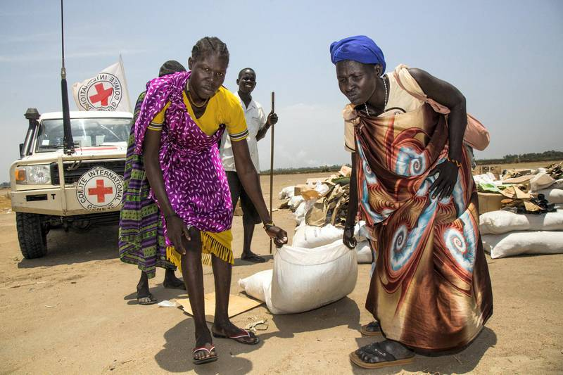 """Women carry a sack of seeds distributed by the International Committee of the Red Cross (ICRC) in the opposition controlled town of Thonyor, in Leer county, on April 11, 2017. - The United Nations warned on APril 11 of a growing risk of mass deaths from starvation among people living in conflict and drought-hit areas of the Horn of Africa, Yemen and Nigeria. An """"avoidable humanitarian crisis... is fast becoming an inevitability"""", as the UN faces a """"severe"""" funding shortfall to help people affected by famine, said UN refugee agency spokesman Adrian Edwards. UNHCR's operations in famine-hit South Sudan, and in Nigeria, Somalia and Yemen, which are on the brink of famine, are funded at between just three and 11 percent, he told reporters in Geneva. (Photo by Albert Gonzalez Farran / AFP)"""