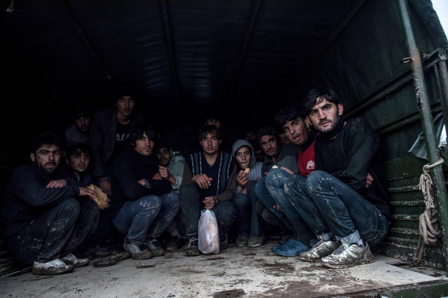 TOPSHOT - Afghan refugees collected by Turkish border army sit in the truck after being deported by Greek army officers on December 9, 2018, near Greece border in Edirne. (Photo by BULENT KILIC / AFP)