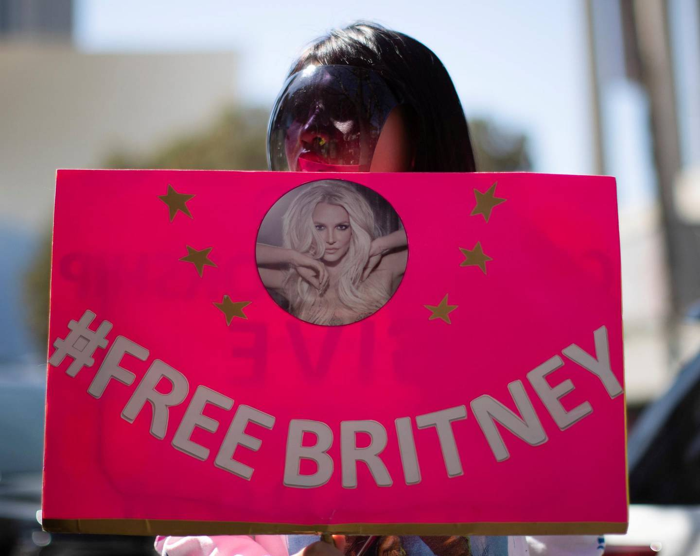 FILE PHOTO: A supporter wearing a personal protective face shield holds a sign while rallying for pop star Britney Spears during a conservatorship case hearing at Stanley Mosk Courthouse in Los Angeles, California, U.S., March 17, 2021.  REUTERS/Mario Anzuoni/File Photo
