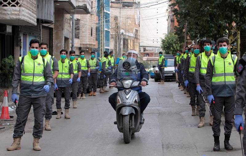 Volunteers from Hezbollah's Islamic health unit stand in preparation to sanitize streets as precaution against the spread of coronavirus disease (COVID-19), during a media tour organised by Hezbollah officials in Beirut's southern suburb, Lebanon March 31, 2020. Picture taken March 31, 2020. REUTERS/Aziz Taher