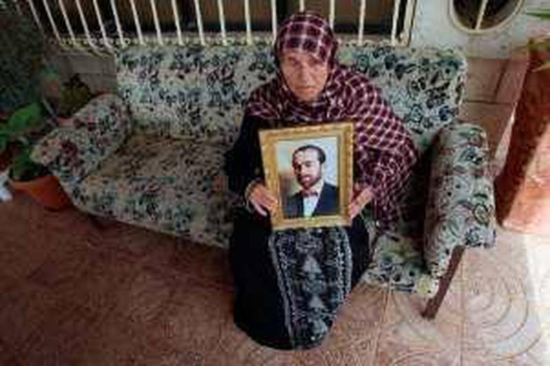 The mother of Maher Uda, a top Hamas commander arrested by Israel in the West Bank overnight, shows journalists a framed picture of her 47-year-old son at the family's home in the village of Ein Yabrud near Ramallah on March 14, 2010. Uda, a senior commander in Hamas's armed wing in the occupied territory, has been arrested by the Israeli security services after more than a decade on the run, an Israeli military spokesman announced. A Palestinian security official in the West Bank said his forces did not know of Uda's whereabouts because he had gone underground several years ago and said they had yet to determine where exactly he was arrested.    AFP PHOTO/ABBAS MOMANI *** Local Caption ***  081077-01-08.jpg