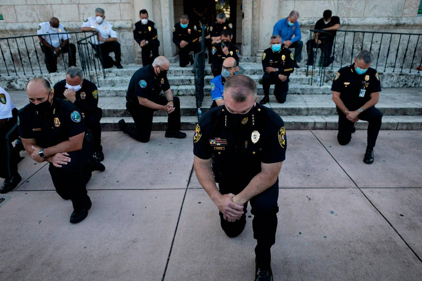 """-- AFP PICTURES OF THE YEAR 2020 --  Police officers kneel during a rally in Coral Gables, Florida on May 30, 2020 in response to the recent death of George Floyd, an unarmed black man who died while being arrested and pinned to the ground by a Minneapolis police officer. Clashes broke out and major cities imposed curfews as America began another night of unrest Saturday with angry demonstrators ignoring warnings from President Donald Trump that his government would stop violent protests over police brutality """"cold."""" -   / AFP / Eva Marie UZCATEGUI"""