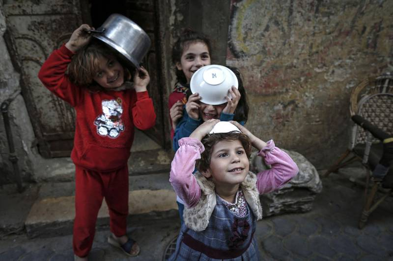 Girls play as Palestinian Walid al-Hattab (unseen) distributes soup to people in need during the Muslim fasting month of Ramadan in Gaza City on April 14, 2021, amid the COVID-19 pandemic. / AFP / Mohammed ABED