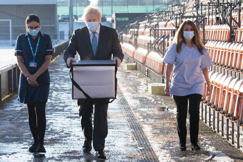 LONDON, ENGLAND - JANUARY 25: British Prime Minister Boris Johnson carries doses of the Oxford/AstraZeneca coronavirus vaccine for mobile distribution at Barnet FC's ground, The Hive, north London, which is being used as a coronavirus vaccination centre on January 25, 2021 in London, England. Government figures show that 6.3 million people across the UK have received their first dose of the coronavirus vaccine, as 32 more vaccination centres open across England. (Photo by Stefan Rousseau - WPA Pool/Getty Images)