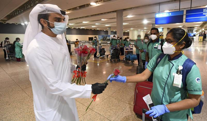 An Emirati official presents a rose to an Indian health worker, part of an 80 person medical team, upon their arrival at Dubai International Airport on May 9, 2020.  / AFP / Karim SAHIB