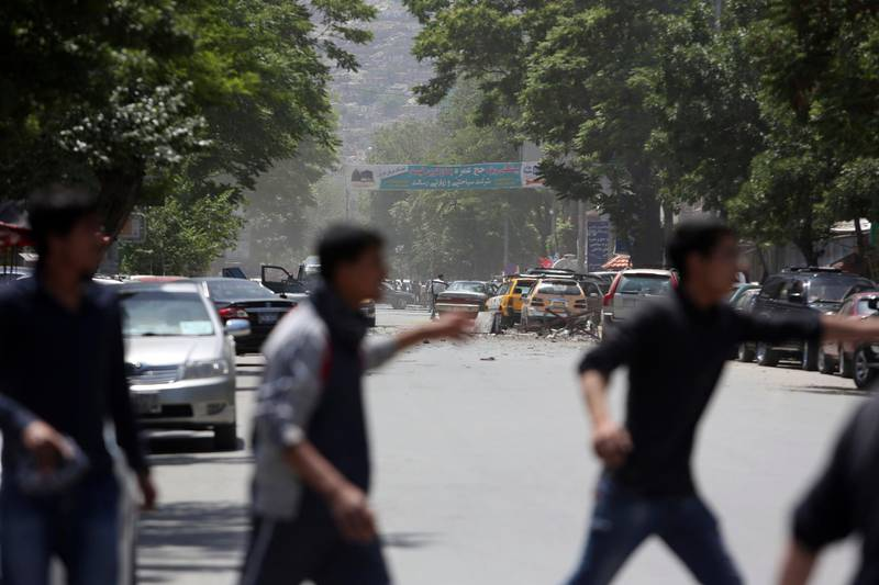 Afghans run from the site of a suicide attack, in the center of Kabul, Afghanistan, Wednesday, May 9, 2018. Three suicide bombers struck two police stations in Afghanistan's capital on Wednesday, wounding at least six people, officials said. (AP Photo/Rahmat Gul)