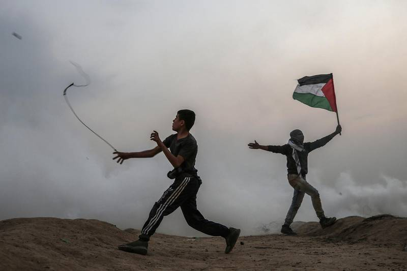 epaselect epa07199867 A Palestinian protester throws stones at Israeli troops during the clashes after Friday protests near the border between Israel and Gaza Strip in the east Gaza Strip, 30 November 2018. Protesters plan to call for the right of Palestinian refugees across the Middle East to return to homes they fled in the war surrounding the 1948 creation of Israel.  EPA/MOHAMMED SABER
