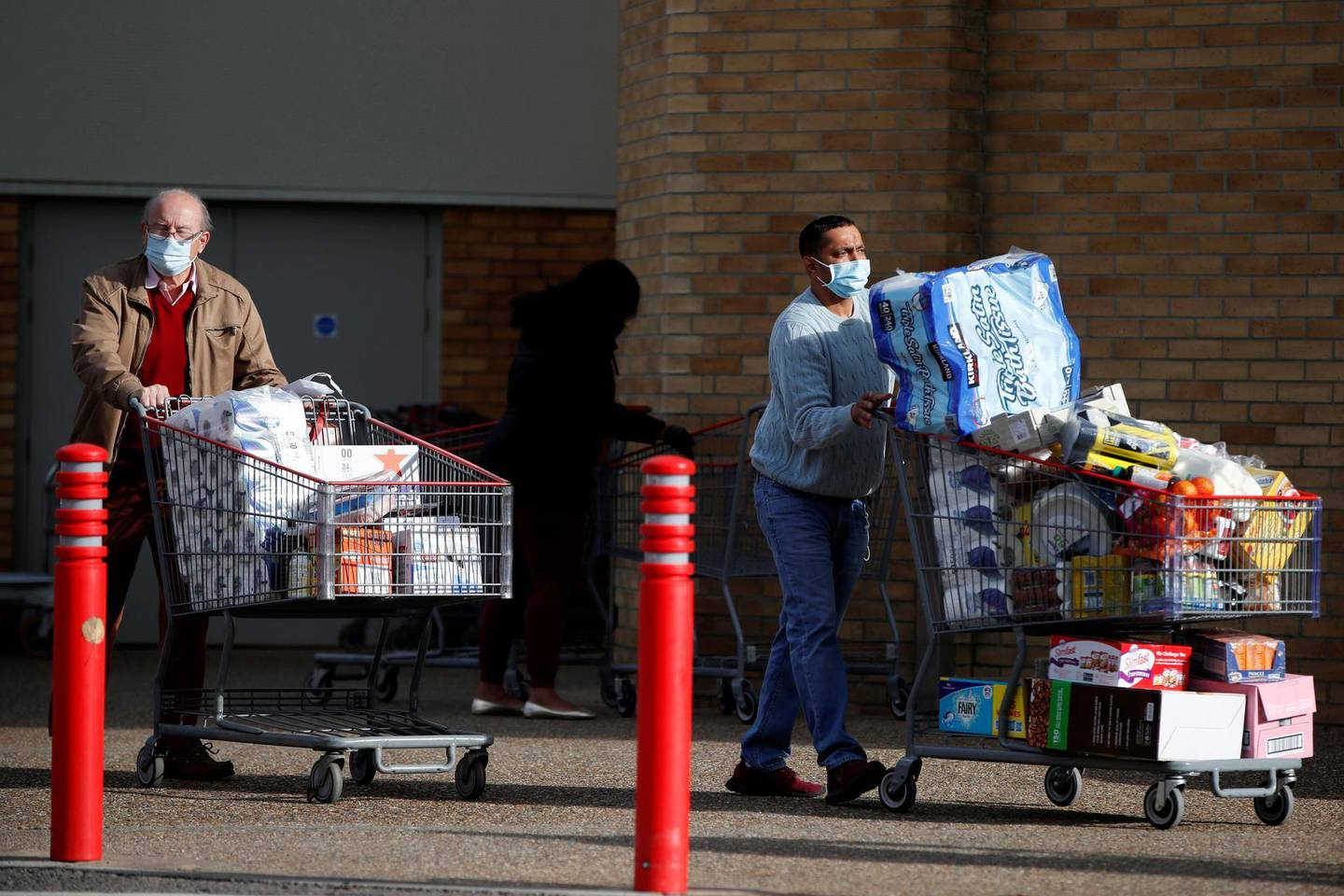 FILE PHOTO: People push full shopping carts outside a store after new nationwide restrictions were announced during the coronavirus disease (COVID-19) outbreak in Watford, Britain, November 2, 2020. REUTERS/Paul Childs/File Photo