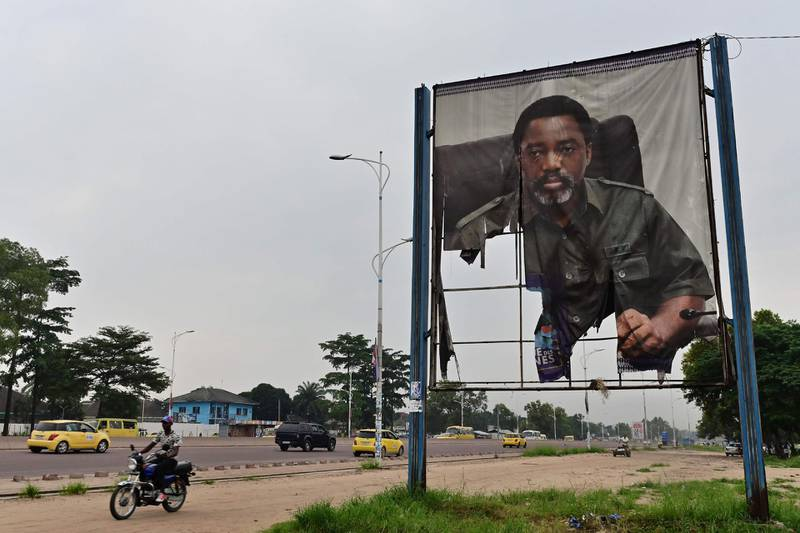 """A man rides his motorcycle past a torned portrait of DR Congo's former president Joseph Kabila, on January 14, 2019, in the Nimite neighbourhood of the capital Kinshasa. Martin Fayulu, who came second in DR Congo's presidential election, has appealed to the Constitutional Court to annul the provisional result which awarded victory to his opposition rival Felix Tshisekedi, his lawyer said on January 12. Fayulu denounced the result as an """"electoral coup"""" engineered by Kabila in which Tshisekedi was """"totally complicit"""", saying the truth of what happened at the ballot box would only come out with a recount. / AFP / TONY KARUMBA"""