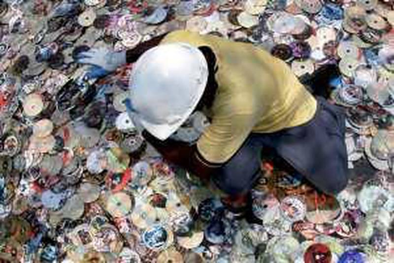 A worker sorts out a portion of about 35,000 confiscated pirated film DVDs as officials prepare to destroy them in the southern Indian city of Chennai March 23, 2007. REUTERS/Babu (INDIA)