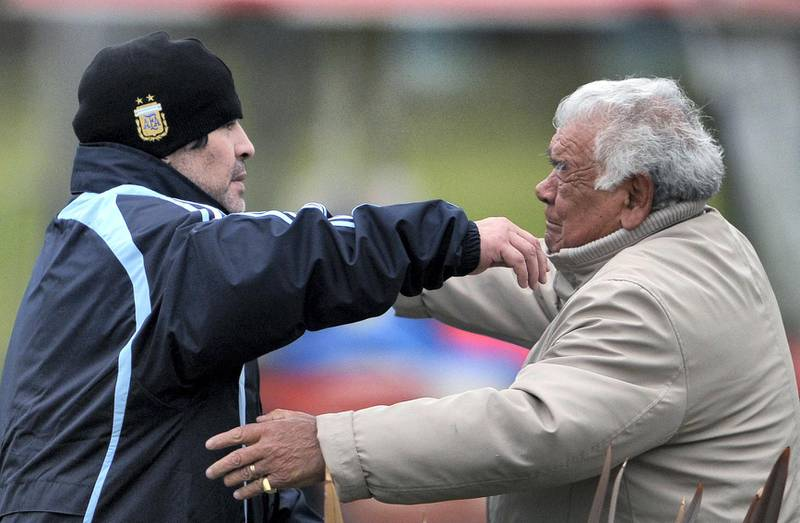 Argentina's National Football team coach Diego Maradona (L) embraces his father Diego at the end of a training session in Buenos Aires on September 3, 2009. Argentina faces Brazil for a FIFA South Africa World Cup-2010 qualifier football match in Rosario on September 5. AFP PHOTO / Juan Mabromata (Photo by JUAN MABROMATA / AFP)