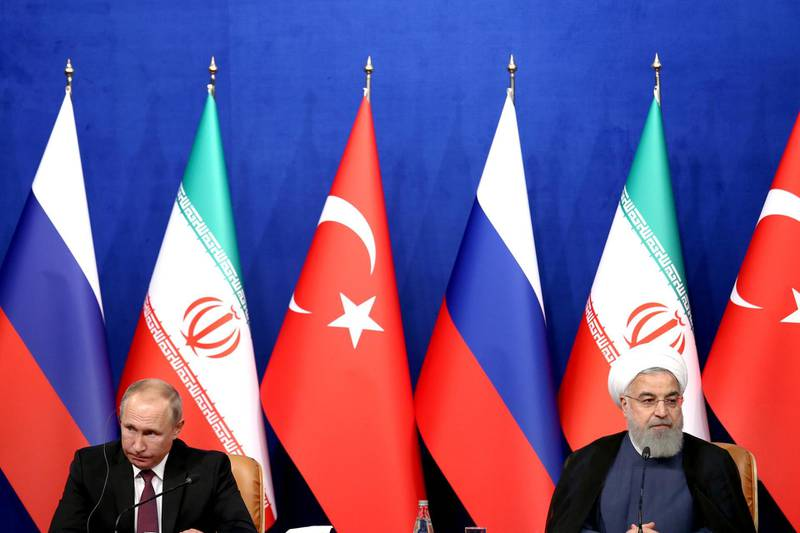 Iran's President Hassan Rouhani, right, speaks in a joint press conference with Russia's President Vladimir Putin, left, and Turkey's President Recep Tayyip Erdogan in Tehran, Iran, Friday, Sept. 7, 2018. Putin, Erdogan and Iran's President Hassan Rouhani began a meeting Friday in Tehran to discuss the war in Syria, with all eyes on a possible military offensive to retake the last rebel-held bastion of Idlib. (AP Photo/Ebrahim Noroozi)