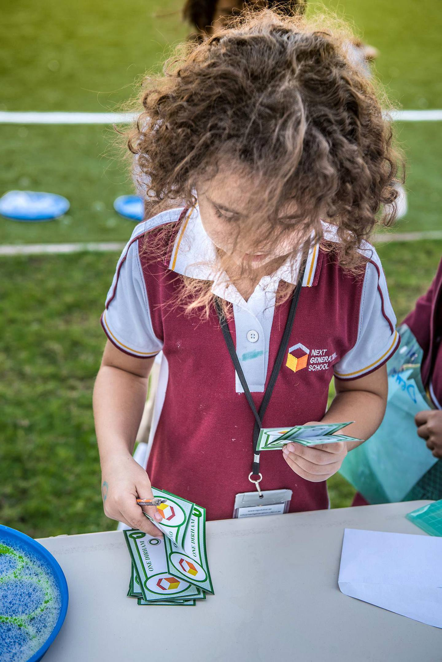 A child at the Next Generation School in Dubai use the in-house currency to buy and sell items at the marketplace. Credit: Courtesy NGS
