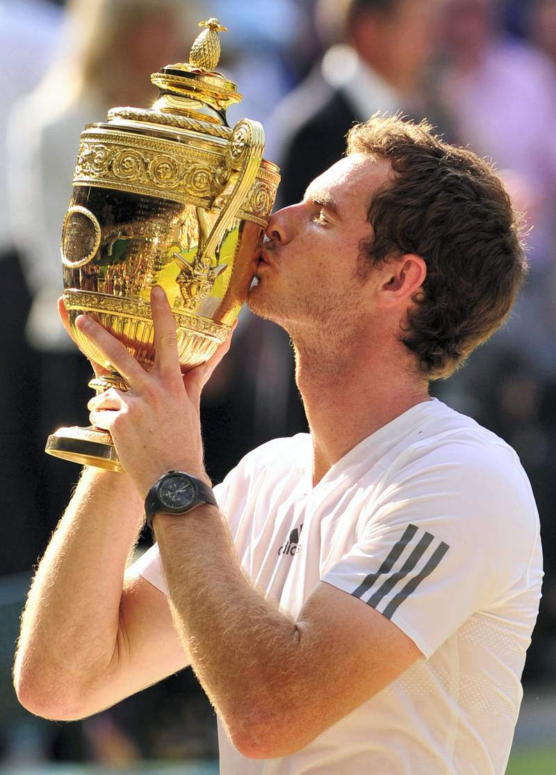Britain's Andy Murray kisses the winner's trophy after beating Serbia's Novak Djokovic in the men's singles final on day thirteen of the 2013 Wimbledon Championships tennis tournament at the All England Club in Wimbledon, southwest London, on July 7, 2013. Murray won 6-4, 7-5, 6-4. AFP PHOTO / GLYN KIRK  - RESTRICTED TO EDITORIAL USE (Photo by GLYN KIRK / AFP)