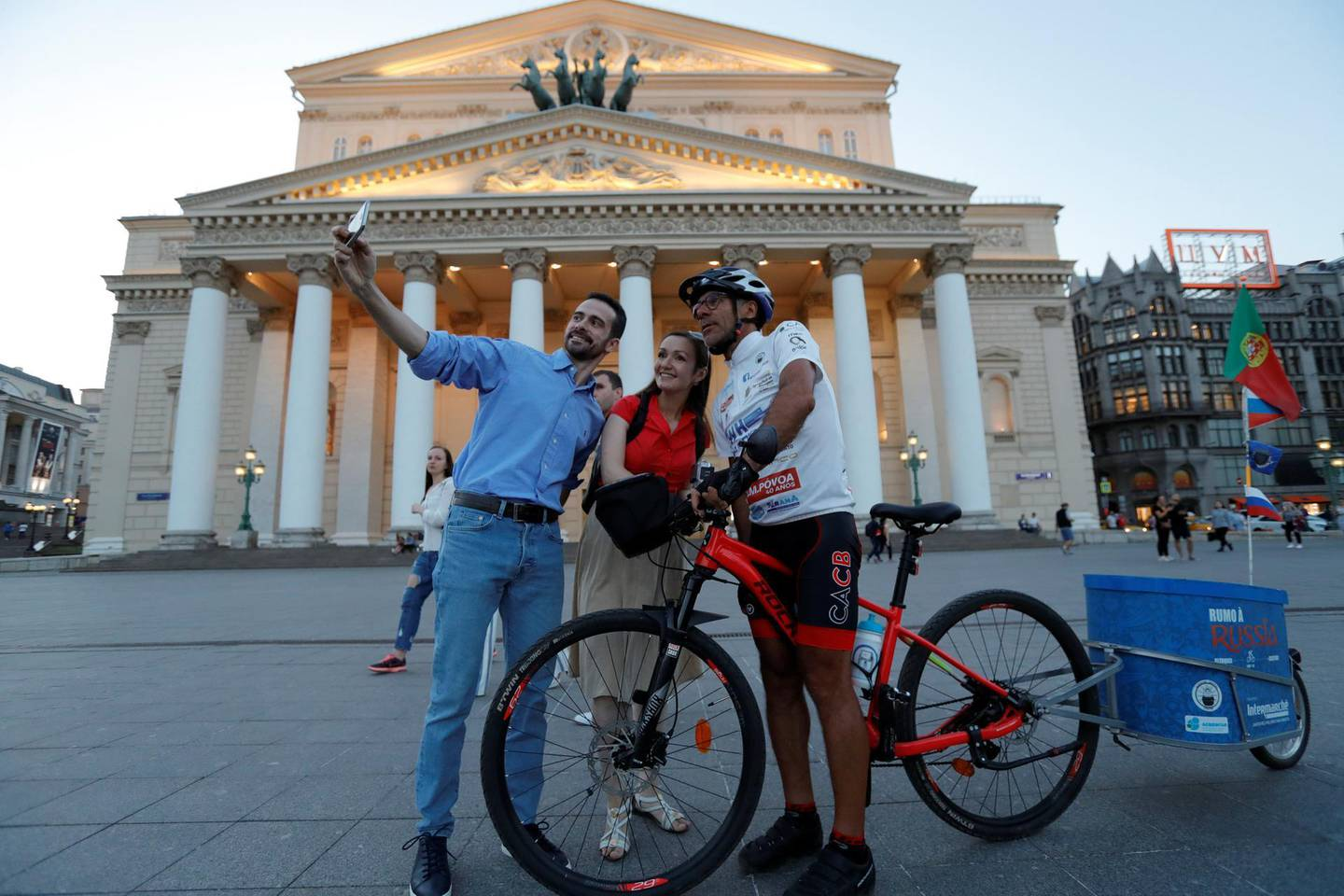 Portuguese cyclist Helder Batista, who arrived in Russia's capital to attend the 2018 FIFA World Cup, poses for a selfie with pedestrians in front of the Bolshoi Theatre in central Moscow, Russia June 18, 2018. REUTERS/Tatyana Makeyeva