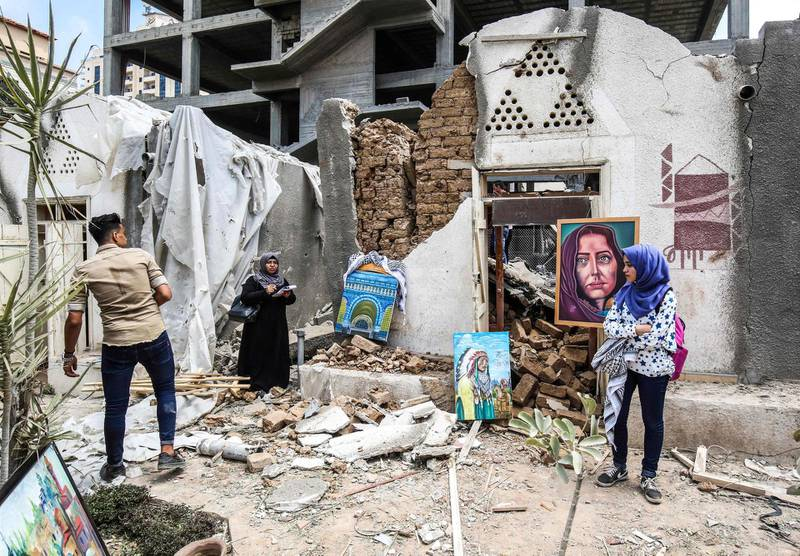 Palestinian artists display artwork in the yard of the damaged Arts and Crafts Village, which was hit by Israeli air strikes two days before, in Gaza City on July 16, 2018.  / AFP / SAID KHATIB
