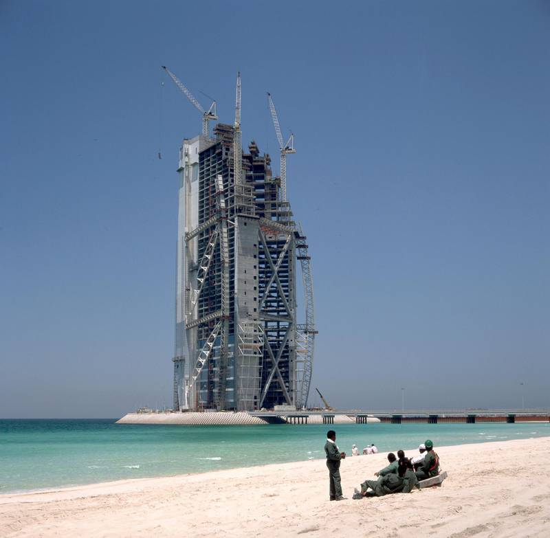ca. 1980-1997, Dubai, United Arab Emirates --- Indian workmen relax in front of the Chicago Beach Hotel tower, the tallest building in the United Arab Emirates. --- Image by © James Davis/Eye Ubiquitous/Corbis  FOR FRIDAY NOV 30, 2013 NATIONAL DAY STORY IN BIZ *** Local Caption ***  bz29no-ND-Hotels-03.jpg