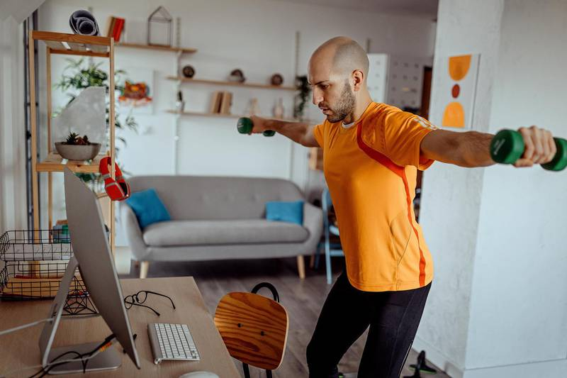 Young man exercising with dumbbells at home, while watching exercise training video online on laptop at home. Getty Images