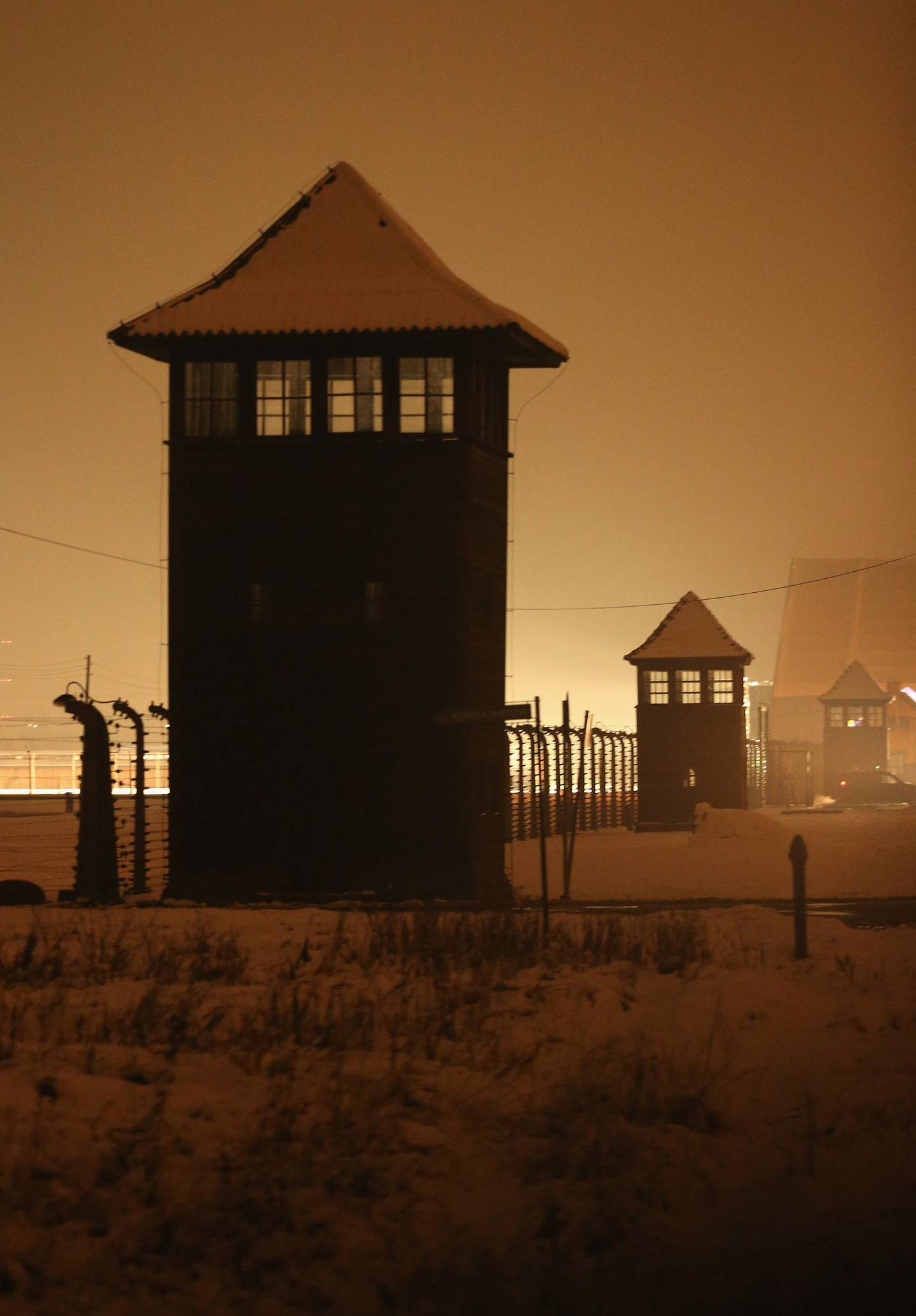OSWIECIM, POLAND - JANUARY 26:  Guard towers and barbed wire fences stand at the former Auschwitz-Birkenau concentration camp on the night prior to commemoration events marking the 70th anniversary of the liberation of the camp on January 26, 2015 in Oswiecim, Poland. International heads of state, dignitaries and over 300 Auschwitz survivors will commemorate the 70th anniversary of the liberation of Auschwitz by Soviet troops in 1945 on January 27. Auschwitz was among the most notorious of the concentration camps run by the Nazis to enslave and kill millions of Jews, political opponents, prisoners of war, homosexuals and Roma.  (Photo by Sean Gallup/Getty Images)