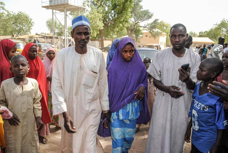 A girl released by Boko Haram walks with his father (L) in Dapchi on March 21, 2018.  Boko Haram Islamists who kidnapped 110 schoolgirls in Dapchi, northeast Nigeria, just over a month ago have so far returned 101 of the students to the town, the government said today. / AFP PHOTO / -