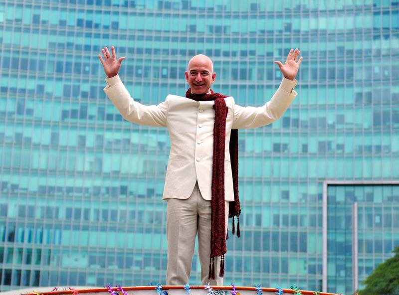 FILE PHOTO: Jeff Bezos, founder and chief executive officer of Amazon, poses as he stands atop a supply truck during a photo opportunity at the premises of a shopping mall in Bangalore, India, September 28, 2014. REUTERS/Abhishek N. Chinnappa/File photo
