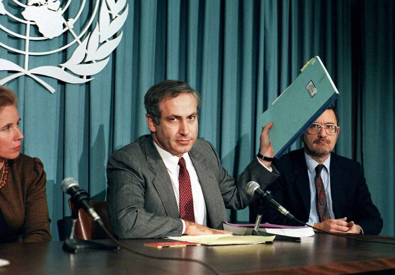Israeli Permanent Representative to the United Nations Ambassador Benjamin Netanyahu holds up a file on Nazi criminal Alois Brunner at a news conference at the U.N. 6 November 1987. Netanyahu was discussing the opening of the U.N. Nazi War Crimes Archives. (Photo by DON EMMERT / AFP)