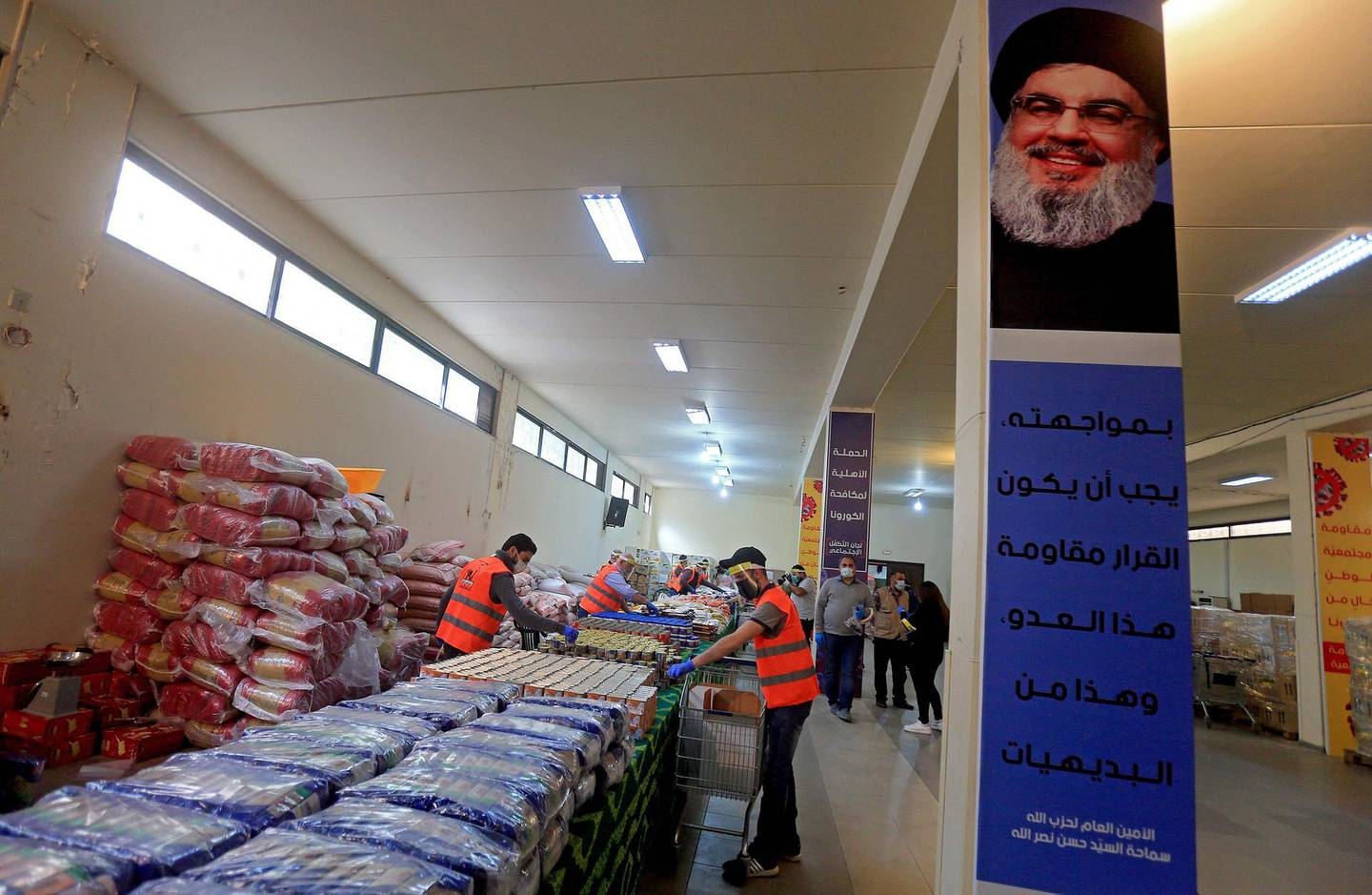 A picture taken during a guided tour organised by the Lebanese Shiite movement Hezbollah shows volunteers sorting food aid that will be distributed to improvised people during the COVID-19 coronavirus pandemic, at a centre in Beirut's southern suburbs on March 31, 2020. / AFP / -