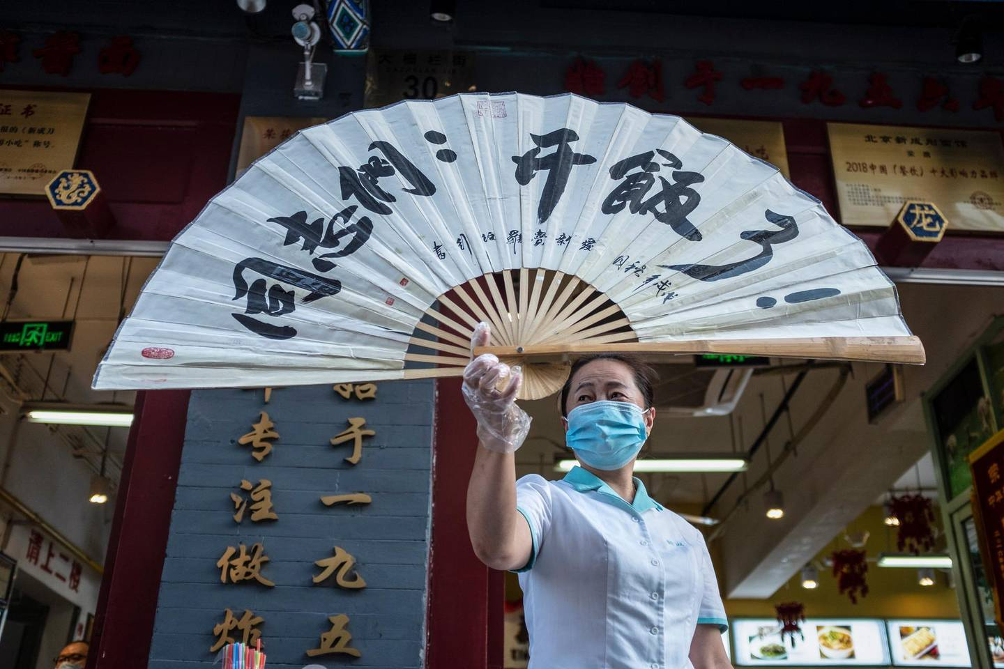 epa08444685 A waitress wearing a protective face mask holds a folding fan reading 'comrades, time for meal' outside a restaurant in Beijing, China, 26 May 2020.  EPA/WU HONG