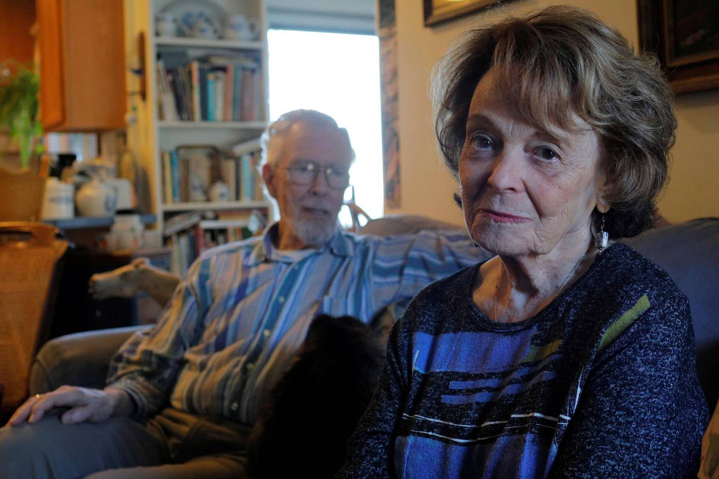 Cynthia Flagg (R) sits with her husband Charles, who took part in an early stage trial of Biogen's drug Aducanumab following his diagnosis with Alzheimer's disease, at their home in Jamestown, Rhode Island, U.S., February 21, 2020.  On June 7, 2021 the U.S. Food and Drug Administration (FDA) approved Aduhelm (aducanumab) as the first treatment to target a likely underlying cause of Alzheimer's disease - sticky deposits of a protein called amyloid beta.  Picture taken February 21, 2020.    REUTERS/Brian Snyder