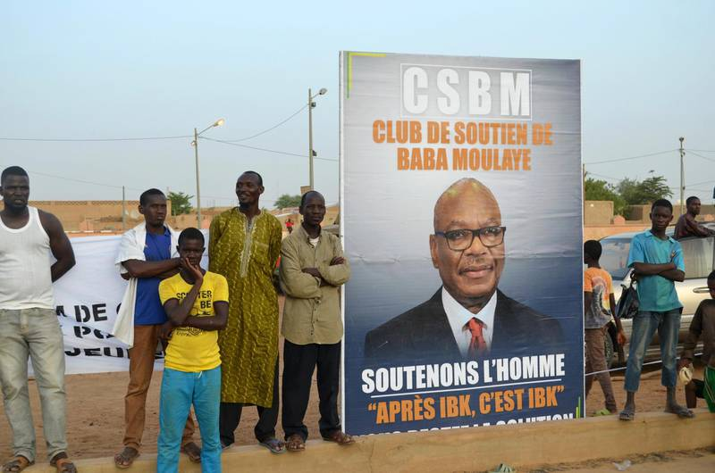 TOPSHOT - Supporters of Malian incumbent president Ibrahim Boubacar Keita wait at the Gao stadium on July 18, 2018 for a presidential campaign rally. / AFP / Souleymane Ag Anara