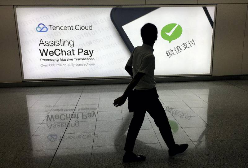 This photo taken on August 21, 2017 shows a man walking at Hong Kong's international airport past an advertisement for the WeChat social media platform owned by China's Tencent company. / AFP PHOTO / Richard A. Brooks