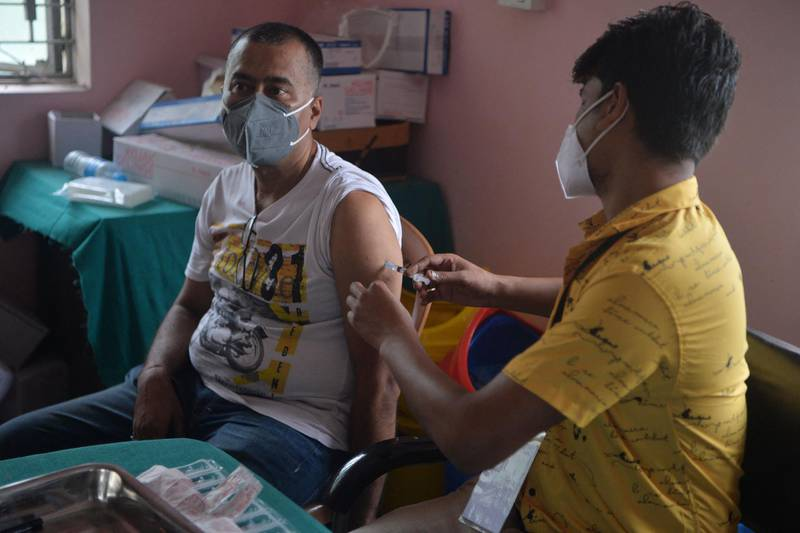 A healthcare worker inoculates a man working in the tourism industry with a dose of the Covishield vaccine against the Covid-19 coronavirus at a primary health centre in Siliguri on June 19, 2021. / AFP / Diptendu DUTTA