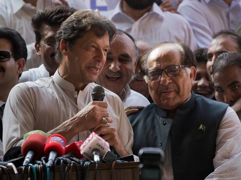Pakistani opposition politician Imran Khan, left, chief of Pakistan Tehreek-e-Insaf party, welcomes senior politician of former prime minister of Pakistan Nawaz Sharif's party, senator Zafar Ali Shah as he joined Khan's party in Islamabad, Pakistan, Thursday, July 5, 2018. Pakistan will hold general election on July 25. (AP Photo/B.K. Bangash)