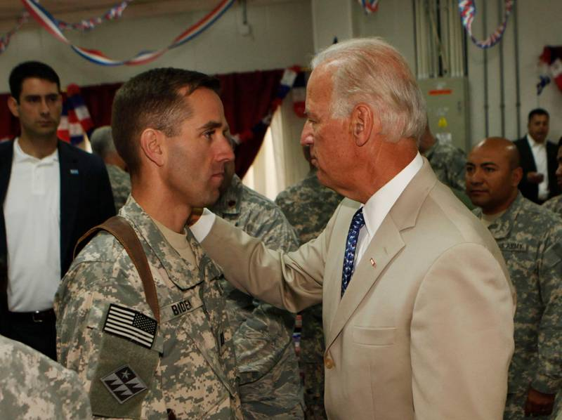 U.S. Vice President Joe Biden (R) talks with his son, U.S. Army Capt. Beau Biden (L) at Camp Victory on the outskirts of Baghdad on July 4, 2009.  Biden said that America's role in Iraq was switching from deep military engagement to one of diplomatic support, ahead of a complete withdrawal from the country in 2011. AFP Photo/ Khalid Mohammed-POOL (Photo by KHALID MOHAMMED / POOL / AFP)