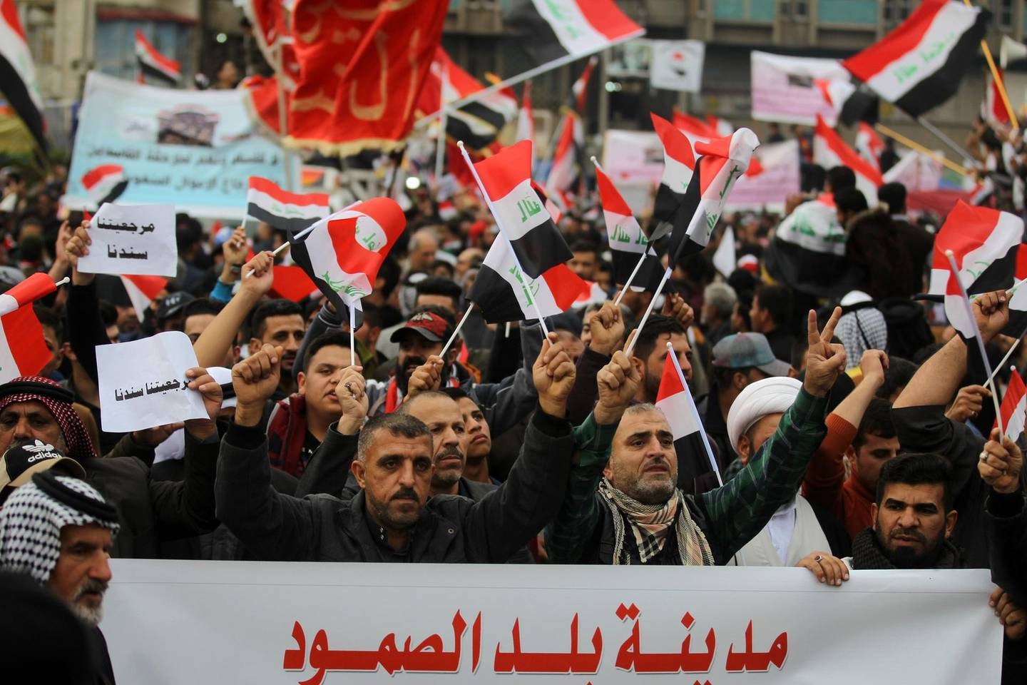 Iraqi demonstrators wave national flags as the take part in an anti-govenment demonstration in the capital Baghdad's Tahrir Square, on December 6, 2019.  Tahrir has become a melting pot of Iraqi society, occupied day and night by thousands of demonstrators angry with the political system in place since the aftermath of the US-led invasion of 2003 and Iran's role in propping it up. / AFP / AHMAD AL-RUBAYE