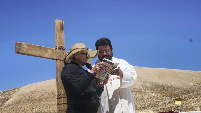 Marie Tawk reads the Bible during mass celebrated by priest Hani Tawk on Qornet Al Sawda, Lebanon, August 9, 2020. Photo by Aram Abdo