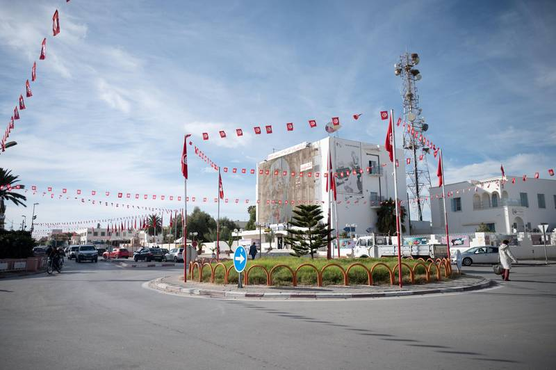 A roundabout in central Sidi Bouzid decorated with Tunisian flags. A giant mural of Mohamed Bouazizi can be seen in the background.