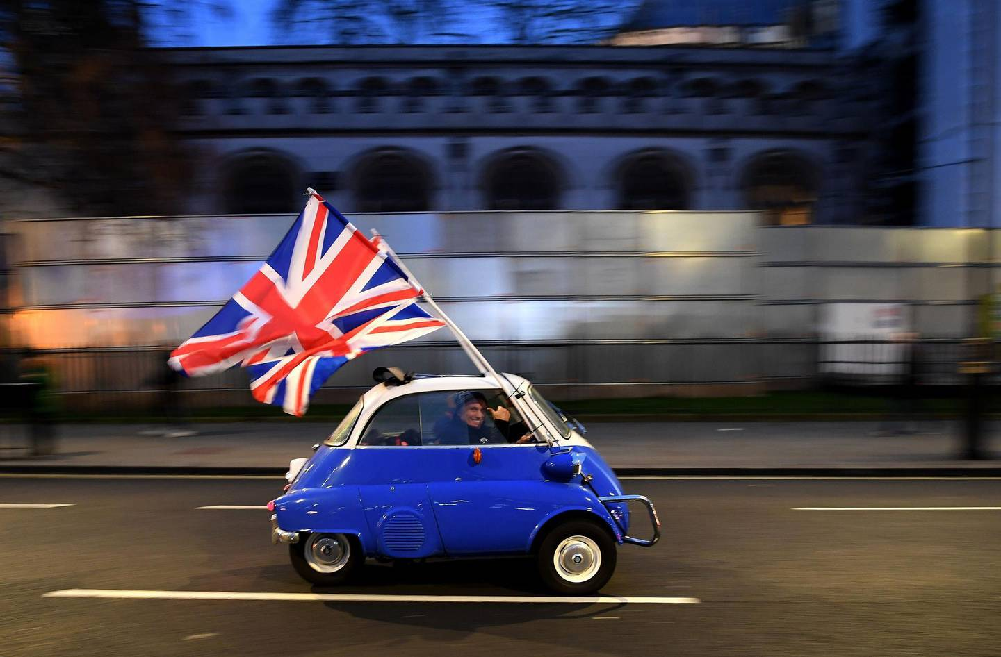 -- AFP PICTURES OF THE YEAR 2020 --  A man waves Union flags from a BMW Isetta as he drives past Brexit supporters gathering in Parliament Square, in central London on January 31, 2020, the day that the UK formally leaves the European Union. Britain on January 31 ends almost half a century of integration with its closest neighbours and leaves the European Union, starting a new -- but still uncertain -- chapter in its long history. -   / AFP / DANIEL LEAL-OLIVAS