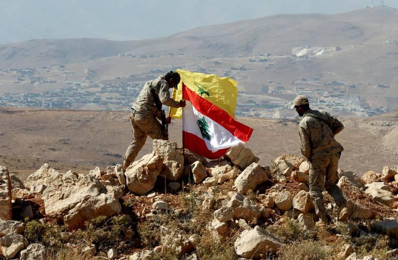 FILE PHOTO: Hezbollah fighters put Lebanese and Hezbollah flags at Juroud Arsal, Syria-Lebanon border, July 25, 2017. REUTERS/Mohamed Azakir/File Photo