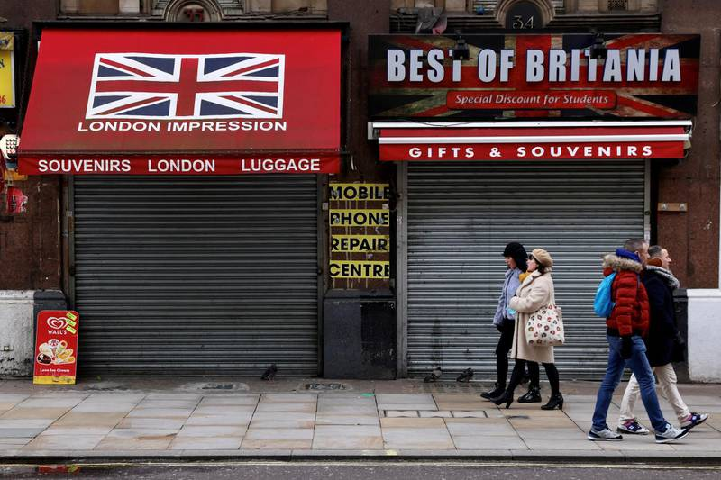 People walk in pairs past closed shops amid the coronavirus disease (COVID-19) pandemic in London, Britain, January 31, 2021.   REUTERS/Kevin Coombs