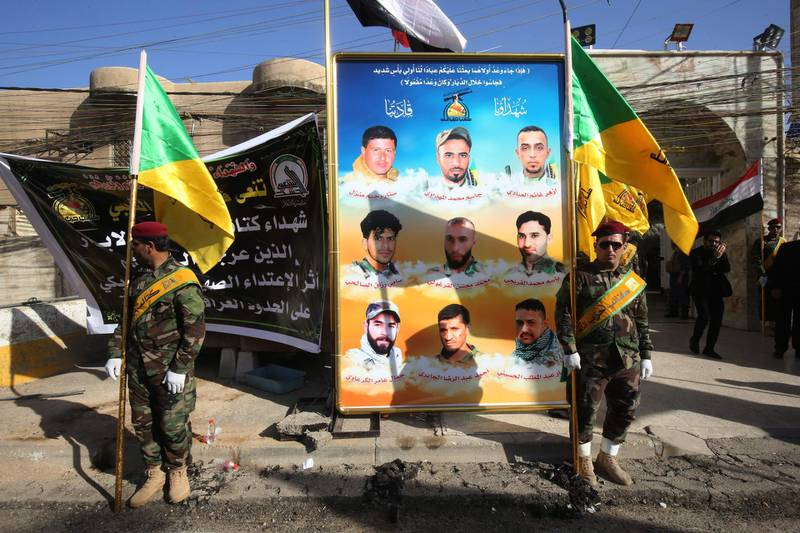 Members of the Iraqi Hezbollah Brigades, part of the Hashed al-Shaabi paramilitary units, carry flags in front of portraits of fellow members who were killed in air raids 4 days earlier, during a memorial ceremony in Baghdad on June 21, 2018.  The air strike that hit targets in eastern Syria near the frontier with Iraq where forces on the ground are battling Islamic State Group (IS) remnants, reportedly left more than 50 people dead, state media and a Britain-based monitor said. Both Damascus and the Iran backed-Hashed have blamed the US-led coalition for the raids, but the coalition and the Pentagon denied any involvement.    / AFP / AHMAD AL-RUBAYE