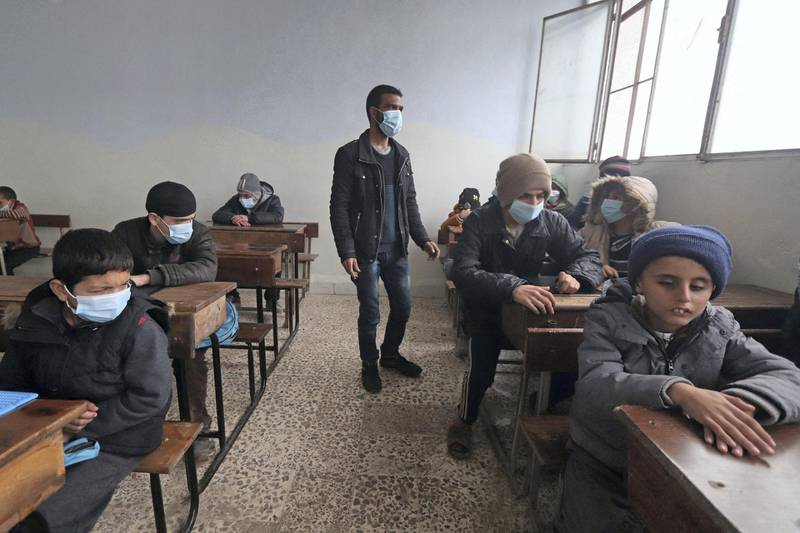 A blind Syrian teacher leads visually impaired pupils during a lesson, respecting social distancing amid the spread of the coronavirus disease (COVID-19), at a school for the blind in the rebel-held northwestern city of Idlib on December 20, 2020. (Photo by Ahmad al-ATRASH / AFP)
