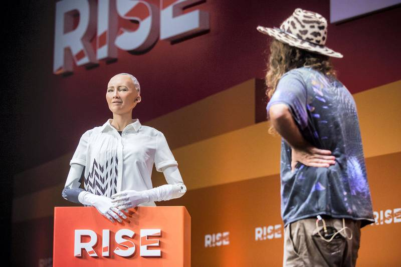 """Chief scientist of Hanson Robotics, Ben Goertzel (R), interacts with """"Sophia the Robot"""" (L) during a discussion about the future of humanity in a demonstration of artificial intelligence (AI) by Hanson Robotics at the RISE Technology Conference in Hong Kong on July 12, 2017. Artificial intelligence is the dominant theme at this year's sprawling RISE tech conference at the city's harbourfront convention centre, but the live robot exchange took the AI debate to another level. / AFP PHOTO / ISAAC LAWRENCE"""