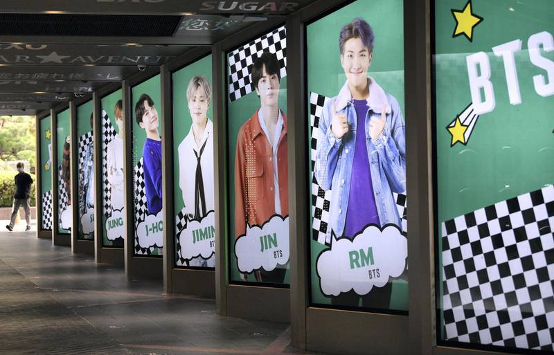 """A man walks past commercial posters showing K-pop group BTS members outside a duty free shop in Seoul on September 1, 2020. - K-pop sensation BTS has become the first all-South Korean act to rule the top US singles chart, industry tracker Billboard announced on August 31, with their English-language """"Dynamite"""" hitting number one. (Photo by Jung Yeon-je / AFP)"""