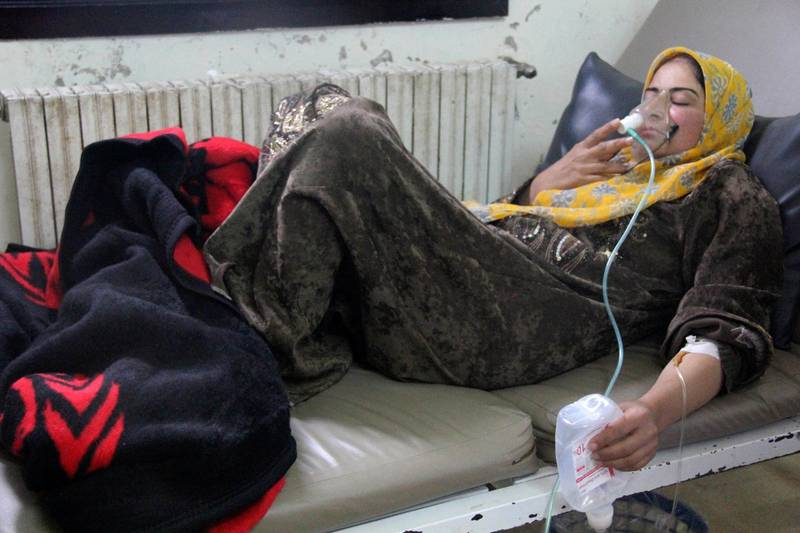 A woman, affected by what activists say was a gas attack, breathes through an oxygen mask inside a field hospital in Kfar Zeita village in the central province of Hama April 12, 2014. Syrian opposition activists have posted photographs and video that they say shows an improvised chlorine bomb to back up claims that President Bashar al-Assad's forces used chemical weapons in two attacks last week. Rebels and the government have blamed each other for the alleged poison gas attacks on Friday and Saturday on rebel-held Kfar Zeita village in the central province of Hama, 125 miles(201 km) north of Damascus. Picture taken April 12, 2014. REUTERS/Stringer (SYRIA - Tags: POLITICS CIVIL UNREST CONFLICT)