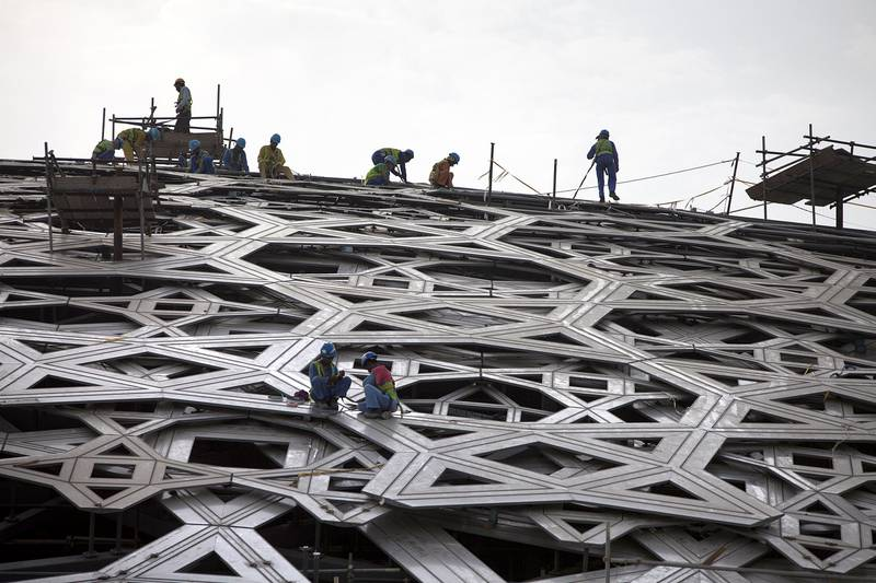 ABU DHABI, UNITED ARAB EMIRATES, July 8, 2015:   Men work on adding the star-shaped elements to the dome at the Louvre Abu Dhabi construction site as seen on Wednesday, July 8, 2015.  (Silvia Razgova / The National)  Section: NA, Usage: RESTRICTED,  *** Local Caption ***  SR-150708-LAD0274.jpg