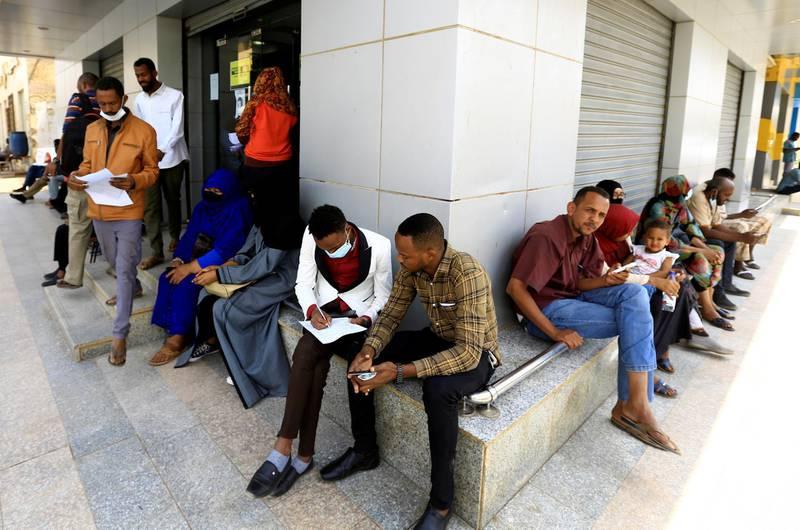 People wait outside currency exchange bureau in Khartoum, Sudan February 28, 2021. REUTERS/Mohamed Nureldin Abdallah